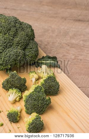 Fresh broccoli with spinach on wooden table close up