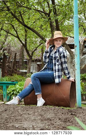 An adorable blonde cowgirl in a straw hat sitting on a rustic iron barrel in the yard