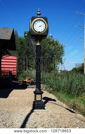 PLAINFIELD, ILLINOIS / UNITED STATES - SEPTEMBER 20, 2015: A clock tells the time outside the old Plainfield Depot.