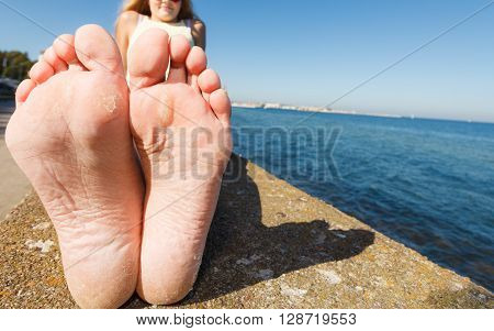 Summer and foot care. Woman relaxing outdoor by seaside showing her dry feet sole wide angle view