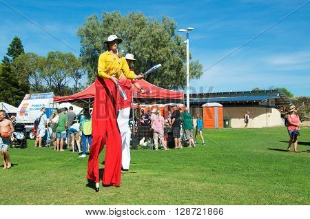 COOGEE,WA,AUSTRALIA-APRIL 3,2016: Lifeguard stilt walkers juggling at the Coogee Beach Festival with families in Coogee, Western Australia.