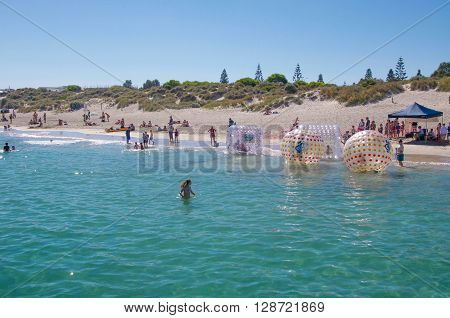 COOGEE,WA,AUSTRALIA-APRIL 3,2016: Coogee Beach Festival scene with families and floating inflatable water balls in the Indian Ocean waters of Coogee, Western Australia.