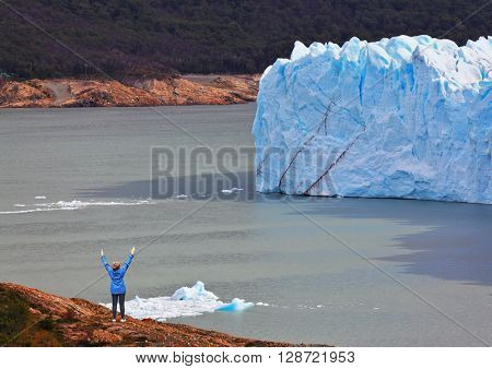 Giant lake Perito Moreno glacier. The woman - tourist admire the white-blue icy splendor