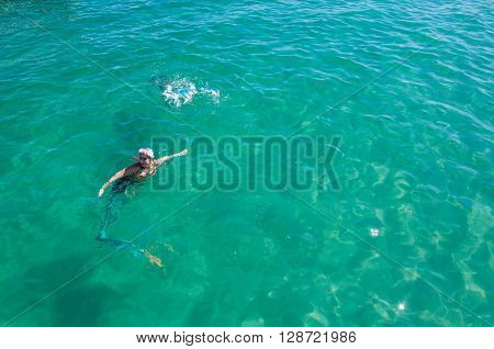 COOGEE,WA,AUSTRALIA-APRIL 3,2016: Live interactive mermaids entertainers in costume swimming in the sea at the Coogee Beach Festival in Coogee, Western Australia.