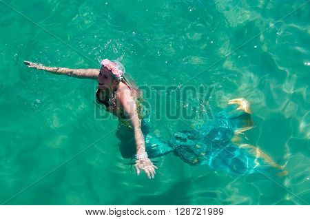 COOGEE,WA,AUSTRALIA-APRIL 3,2016: Live interactive mermaid swimming in the turquoise Indian Ocean at the Coogee Beach Festival in Coogee, Western Australia.