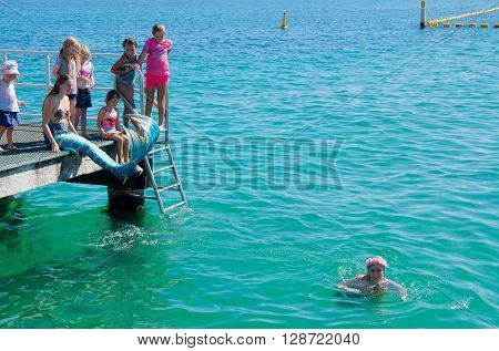 COOGEE,WA,AUSTRALIA-APRIL 3,2016: Live interactive mermaids entertainers in costume on jetty and in Indian Ocean with families at the Coogee Beach Festival in Coogee, Western Australia.