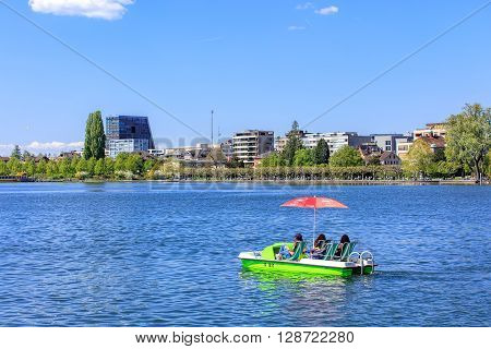 Zug, Switzerland - 6 May, 2016: people in boat on Lake Zug with the city of Zug in the background. Lake Zug (German: Zugersee) is a lake in central Switzerland situated between Lake Lucerne and Lake Zurich.