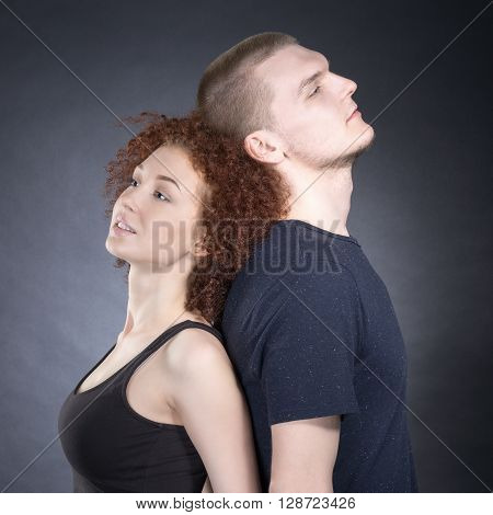 Portrait of happy couple leaning back to back