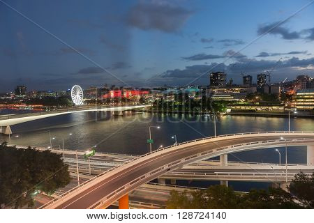 Brisbane, Australia - April 26, 2016: Brisbane night lights over tiered roadways along river and South Bank buildings Captain Cook Bridge  and gaint ferris wheel dark cloudy sky