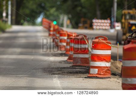 Construction zone with orange caution markers along an urban street.