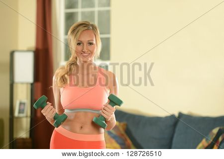 Young Woman working out with dumbbells at home