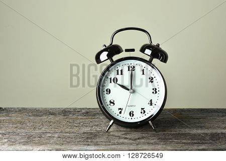 Black alarm clock on the rusty wooden table