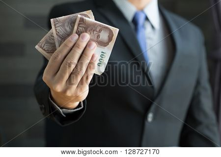 Businessman holding money thai baht in suit is a tidy