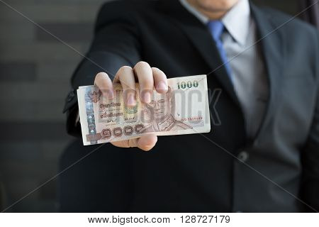 Businessman holding money thai baht in suit a tidy
