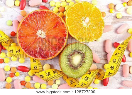 Fresh fruits tape measure medical pills tablets and capsules on rustic wooden background concept of slimming and choice between healthy nutrition and medical supplements