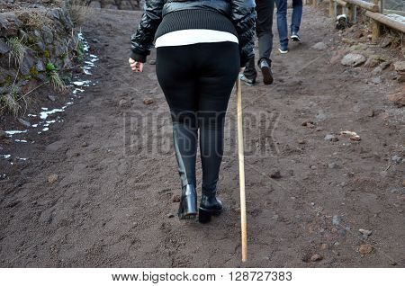 woman with not ideal shoes walking with stick on the volcanic dust path
