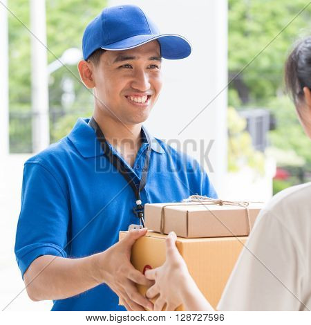 Woman hand accepting a delivery of boxes from deliveryman at home