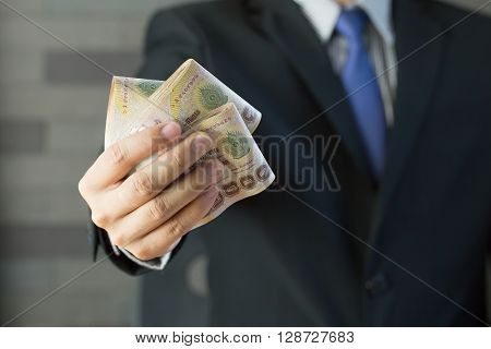 Businessman holding money thai baht in suit and tie