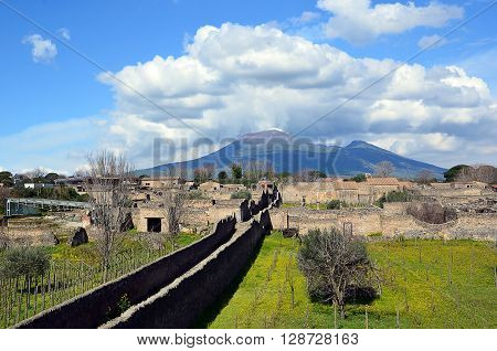 long road and vesuvius cloudy sky from pompei city excavation italy