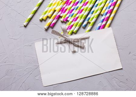 Bright colorful paper straws and empty tag for text on grey textured background. Selective focus. Place for text.