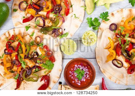 Homemade chicken Fajitas with vegetables lime and salsa sauce on wooden background full focus studio lights top view