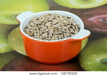 Raw shelled sunflower seeds in an orange ramekin dish.