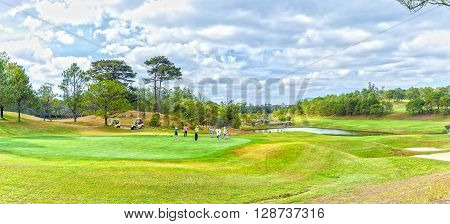 Lam Dong, Vietnam - February 4th, 2015: A family playing golf under valley where vast green pastures interspersed pine forests, fresh water lake really cool, to enjoy holidays in Lam Dong, Vietnam