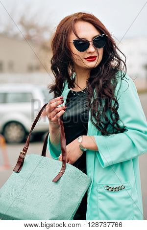 Amazing beautiful girl with dark hair. Fashion handbag, long coat mint color. Stylish sunglasses. Red plump lips, beautiful makeup