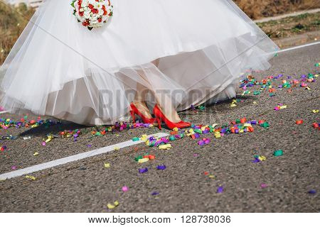 Wedding, bride woman leg in red shoes walking at confetti