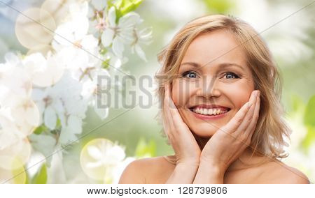 beauty, people and skincare concept - smiling woman with bare shoulders touching face over natural spring cherry blossom background