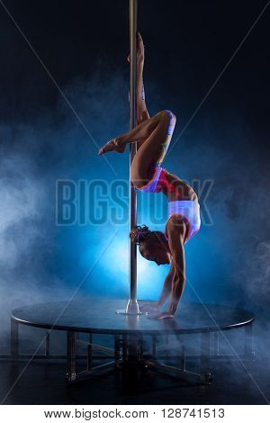 Pole dance. Flexible girl posing while doing handstand