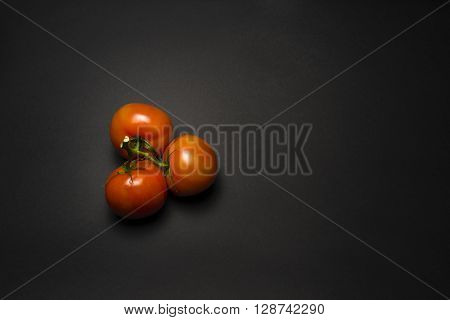 tomatoes on a branch on a black table