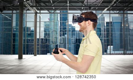 3d technology, virtual reality, entertainment and people concept - happy young man with virtual reality headset playing with game controller gamepad over empty industrial room and city background