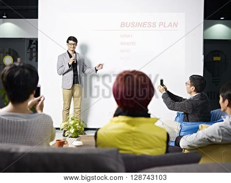 young asian entrepreneur presenting business plan for new project with the audience taking picture with cellphones.