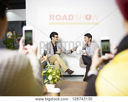 young asian entrepreneur being interviewed while the audience taking pictures using cellphone during roadshow.
