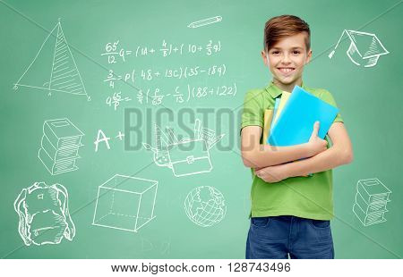 childhood, education and people concept - happy smiling student boy with folders and notebooks over doodles on green chalk board background