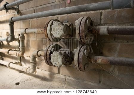 Old dusty and rusty open close valve and pipes on yellow brick wall.