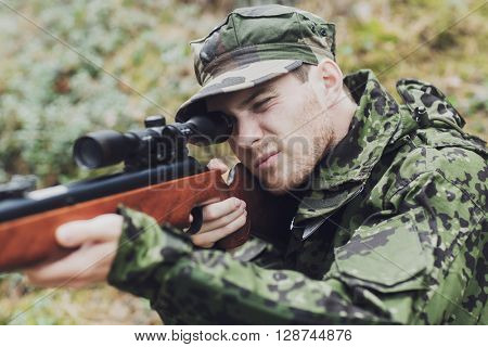 hunting, war, army and people concept - young soldier, ranger or hunter with gun aiming and shooting in forest
