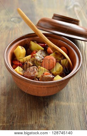 Beef stew with vegetables in a pot, vertical
