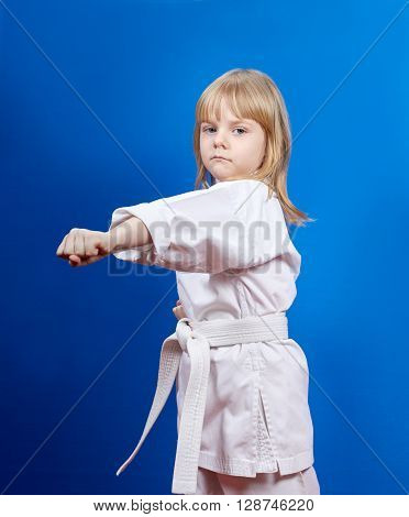 Girl in karategi beats punch arm on the blue background