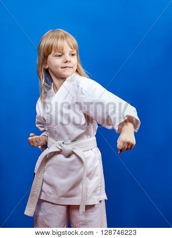 In karategi little athlete beats punch on the blue background