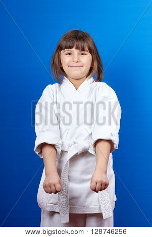In the rack of karate is standing a little  athlete