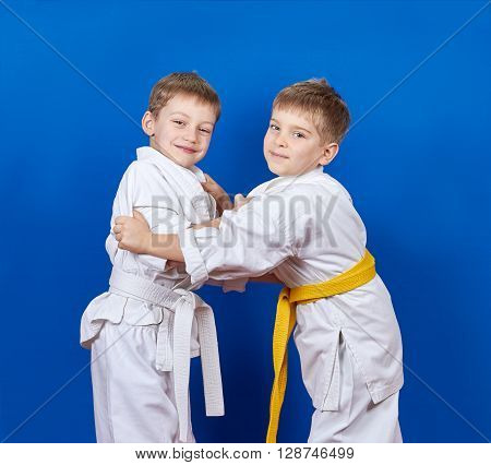 Two athletes train judo techniques on the blue background