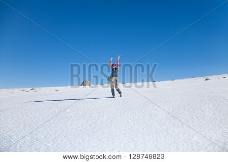 brunette sport active woman with green red and brown clothes hiking looking and arms up gesturing victory in snow with blue sky in Gredos mountain Avila Spain Europe
