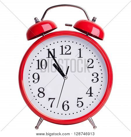 Round red alarm clock is showing almost eleven
