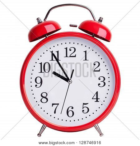 Round red alarm clock shows five minutes to ten