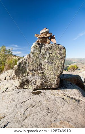 pile or heap of stones several sizes leading mountain path as cairn or milestone and horizon blue sky in Gredos Avila Spain Europe