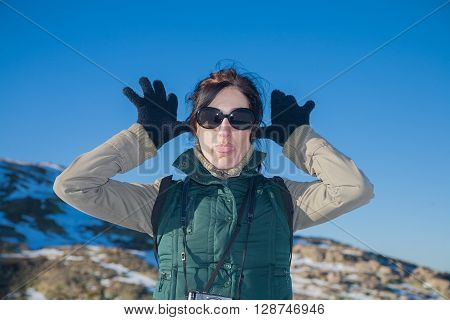portrait of pretty face woman with green vest and sunglasses looking gesturing hands gloves making fun scoff and sticking out tongue in winter outdoor blue sky