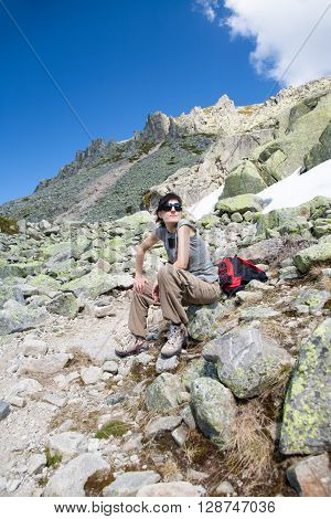brunette sport woman grey shirt red rucksack and sunglasses sitting relaxing and posing looking on rock blue sky with peak mountain behind in Gredos Avila Spain Europe