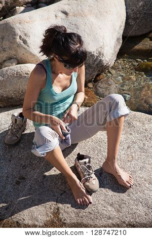 brunette woman green shirt grey trousers barefoot sitting on rock putting on a sock and shoe boot mountain getting ready to hike in summer in Gredos Avila Spain Europe
